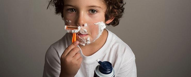 カミソリで髭を剃る子供